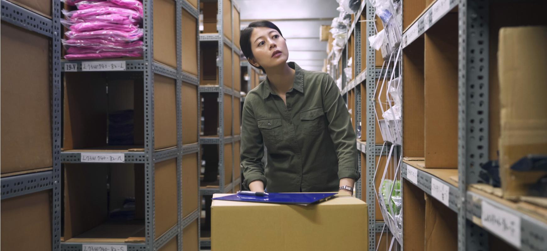 employee pushing boxes in large warehouse
