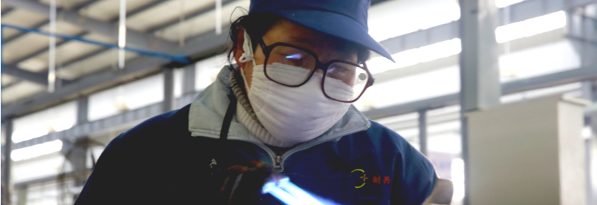Chinese factory worker welding while wearing a mask